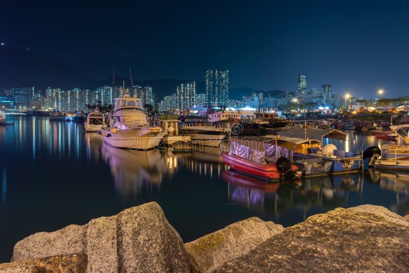 Nattplats av fiskeläget en liten gemenskap med fiskebåtar och nattcityscape på den Lei Yue Mun vattenfjärden arkivbilder