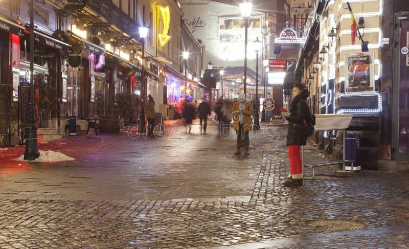 Nattplats av folk som går i gammal stad av Bucharest, Rumänien fotografering för bildbyråer