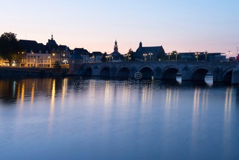 Nattplats av Maastricht och Sten Servaasbridge med lång exponering royaltyfri foto