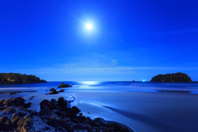 Nattplats: Måne över havet, stranden och öar fotografering för bildbyråer