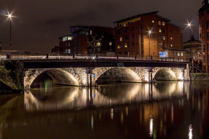 Nattplats med den tända bron över en flod med långa reflexioner royaltyfri foto