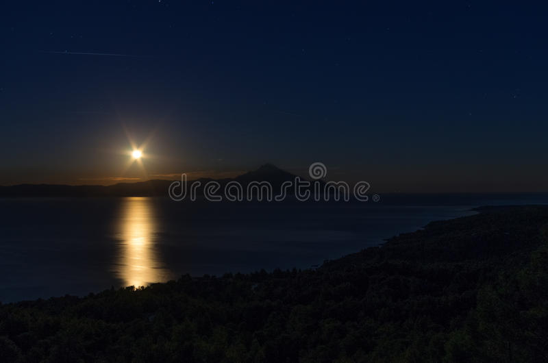 Nattplats med måneresningen i Sithonia, Chalkidiki, Grekland fotografering för bildbyråer