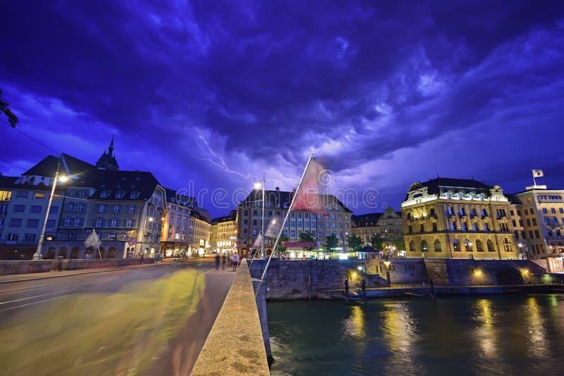 Nattplats plus blixt i himlen av Baseln på den Mittlere Brucke stenbron med den Eisengasse vägen framåt royaltyfria foton