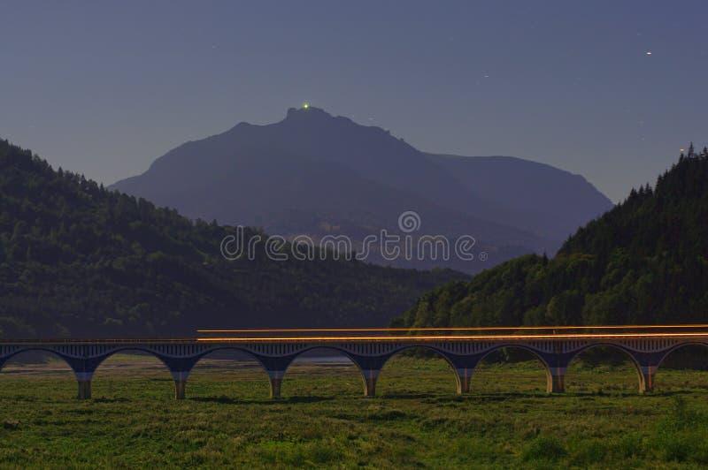 Nattplatsen av viaduktbron med bilen skuggar arkivfoto