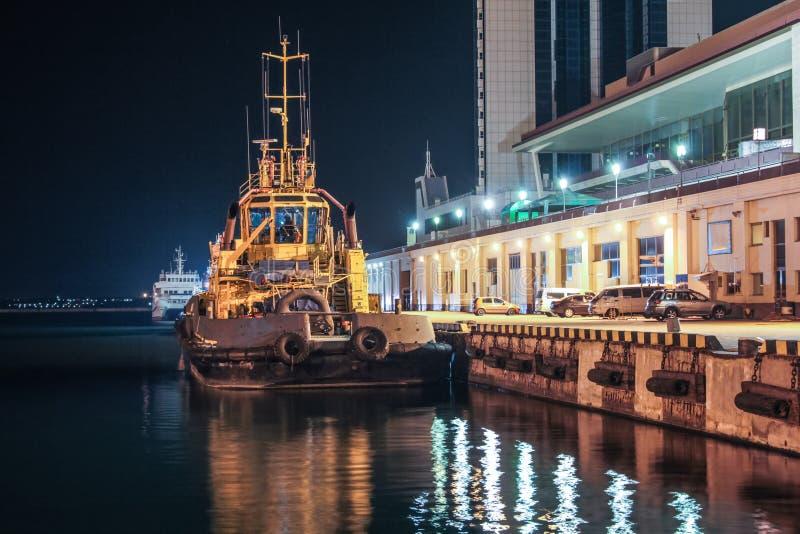 Nattsikt av bogserbåten i lastporten royaltyfri fotografi