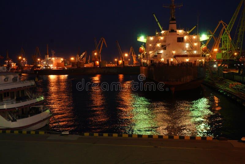 Nattsikt av bogserbåten i lastporten av Odessa Bogserbåtar och en sväva kran är i port Nattpanorama av porten arkivfoton
