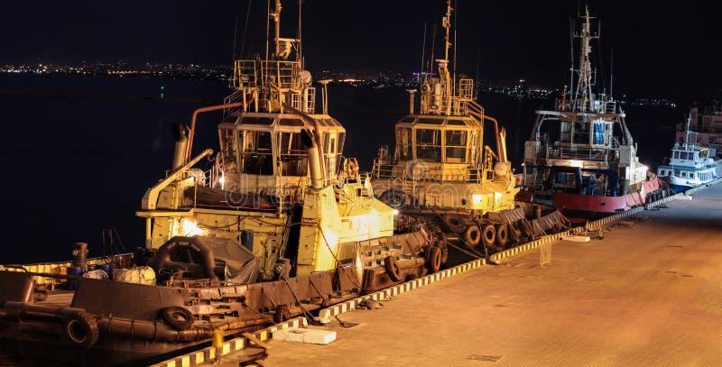 Nattsikt av de tre bogserbåtarna i lastporten arkivfoto