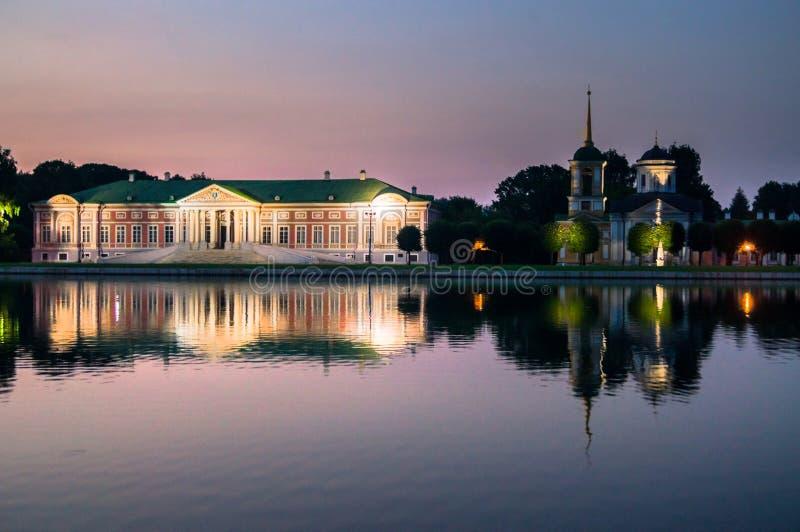 Nattsikt av den aristokratiska herrgården och kyrkan med klockatornet bredvid dammet i museum-godset Kuskovo, Moskva royaltyfri foto