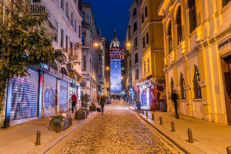 Nattsikt av den gamla smala gatan med det Galata tornet royaltyfria bilder