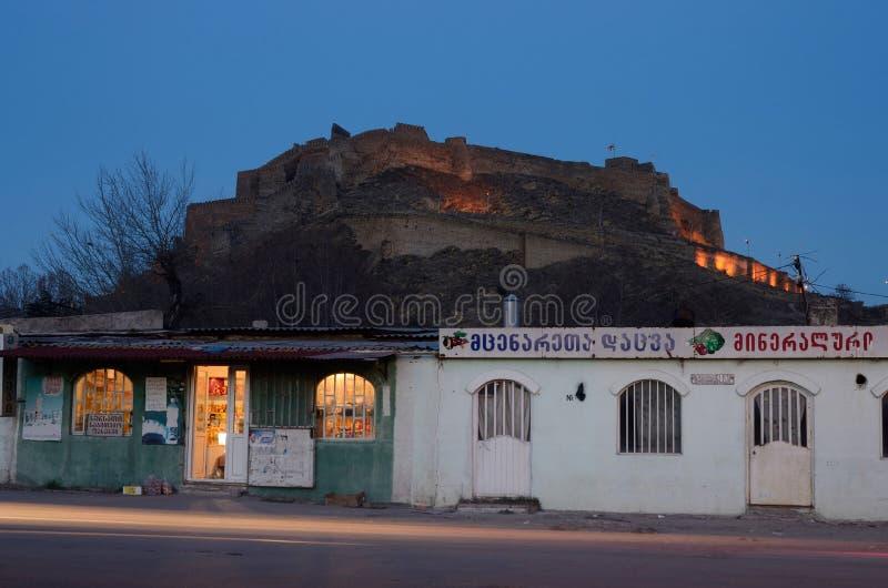 Nattsikt av den Gori fästningen från gatamarknaden, Georgia royaltyfri fotografi