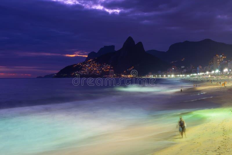 Nattsikt av den Ipanema stranden och berget Dois Irmao (broder två) i Rio de Janeiro royaltyfri bild