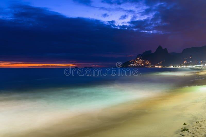 Nattsikt av den Ipanema stranden och berget Dois Irmao (broder två) i Rio de Janeiro arkivbilder