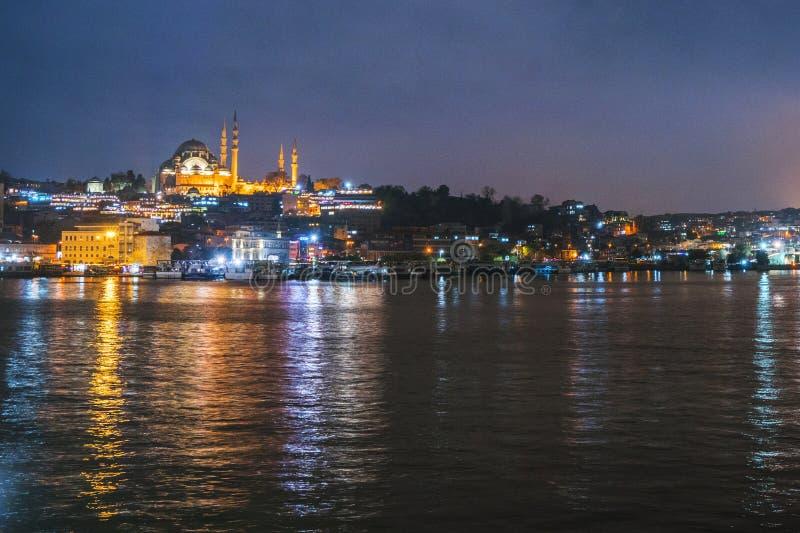 Nattsikt av den Istanbul cityscapeSuleymaniye moskén Rustem Pasha Mosque med att sväva turist- fartyg i Bosphorus, Istanbul arkivfoton