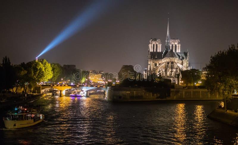 Nattsikt av den Notre Dame domkyrkan med Eiffeltornstrålkastaren arkivbild