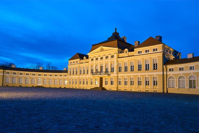 Nattsikt av den upplysta höjden av den barocka historiska slotten arkivbilder