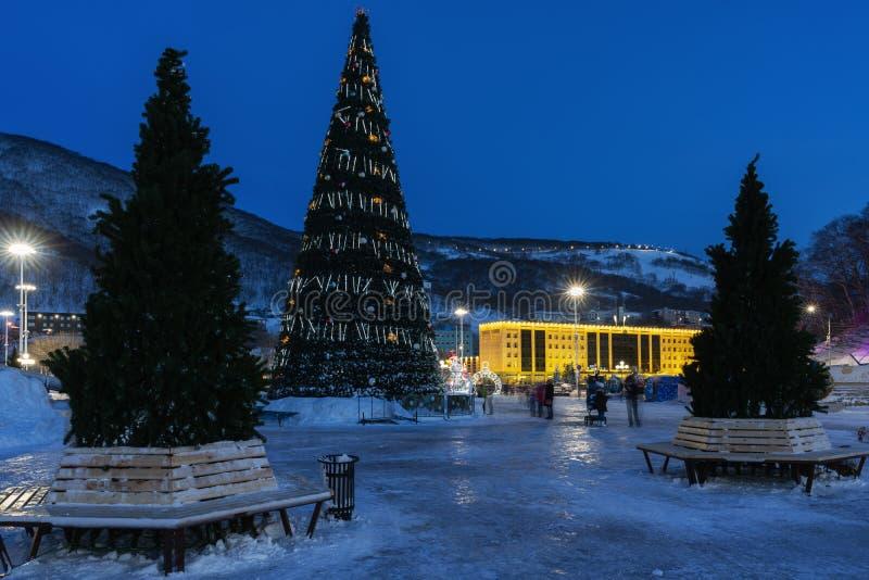 Nattsikt av julgranen i lyckligt nytt år för snöig stad royaltyfri bild