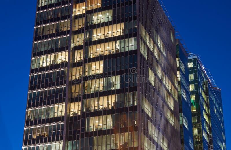 Nattsikt av modern kontorsbyggnad arkivfoto