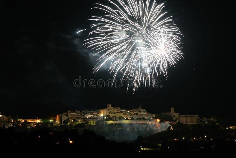 Nattsikt av Montefalco Italien som t?nds av fyrverkerier arkivfoton