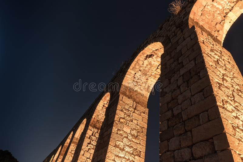 Nattsikt av restna av en forntida romersk akvedukt som lokaliseras mellan tunnlandet och Nahariya i Israel royaltyfria bilder