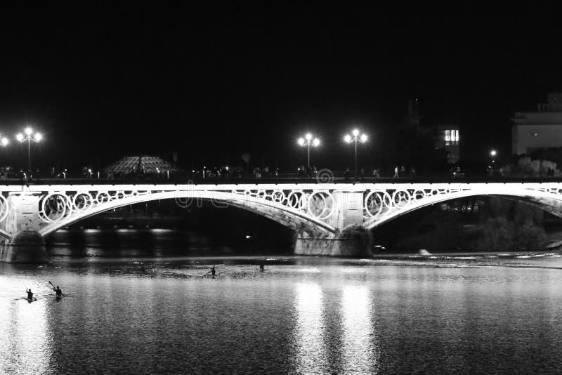Nattsikt av Seville med dess flod Guadalquivir och Torren del Oro arkivfoton
