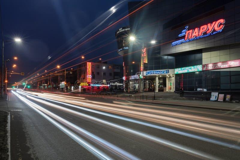 Nattsikt av suddiga spår av bilbillyktor som kör på stadsvägen royaltyfri fotografi
