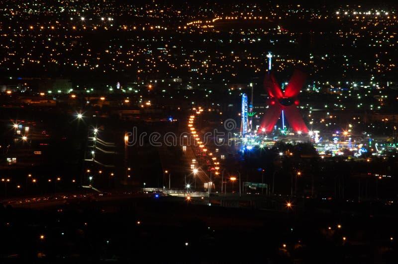 Nattsikt av US-/Mexicogränsen, El Paso TX/Juarez Chihuahua som visar Rio Grande, trafik på bron och en karneval arkivbild