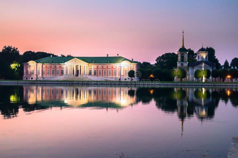 Nattsikt till och med dammet på slotten och kyrkan med klockatornet i museum-godset Kuskovo, Moskva royaltyfri bild