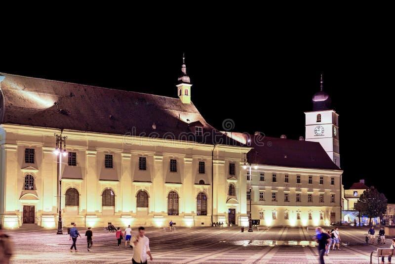 Nattsikt till rådtornet och stor fyrkant med folk royaltyfri foto