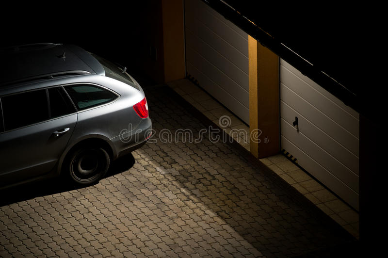 Nattsikten av en bil parkerade framme av garaget royaltyfri foto