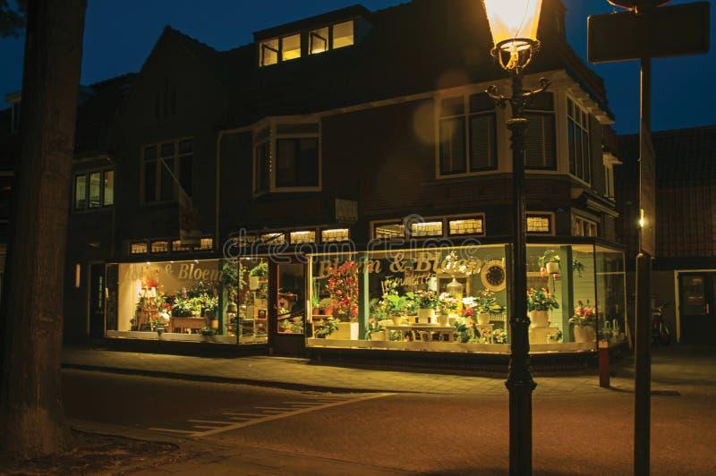 Nattsikten av gatablommor shoppar och tänder lampan i förgrunden på gryning i Weesp fotografering för bildbyråer