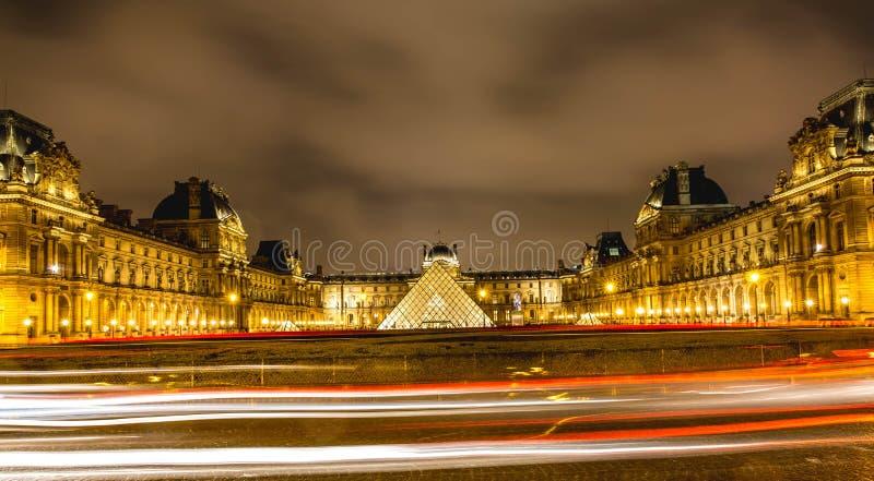 Nattsikten av Louvremuseet i Paris, med billjus skuggar royaltyfri foto