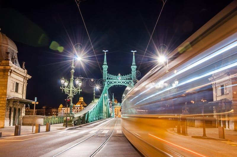 Nattsikten av spårvagnen på Liberty Bridge eller frihetsbron med linsen blossar i Budapest, Ungern arkivfoto