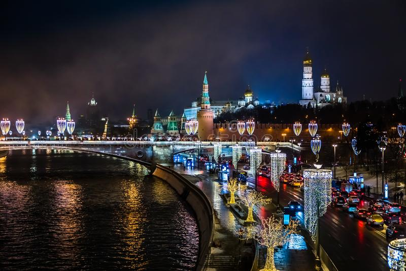 Nattsikten till MoskvaKreml- och flodbanker dekorerade med NY I royaltyfri bild