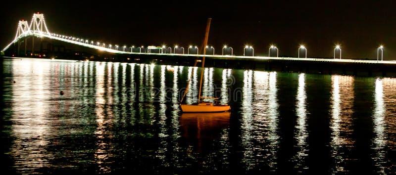 Nattskott av den Newport bron med segelbåten arkivfoton
