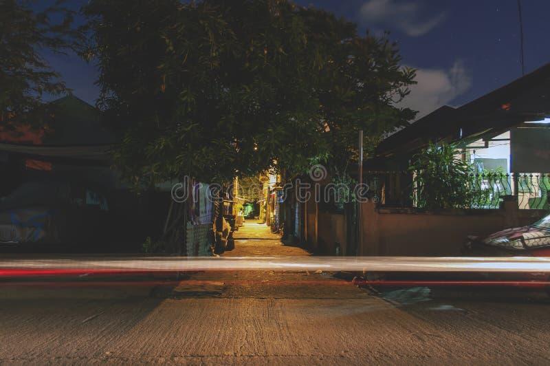 Nattskott på en typisk gata i en stad i Filippinerna med ljus från lampor och hem En enda ljusspår i en bil arkivbild