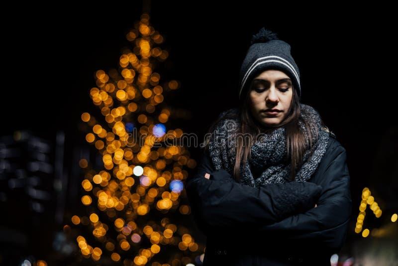 Nattstående av en ledsen kvinna som bara känner sig och som är deprimerad i vinter Vinterfördjupning och ensamhetbegrepp royaltyfri bild