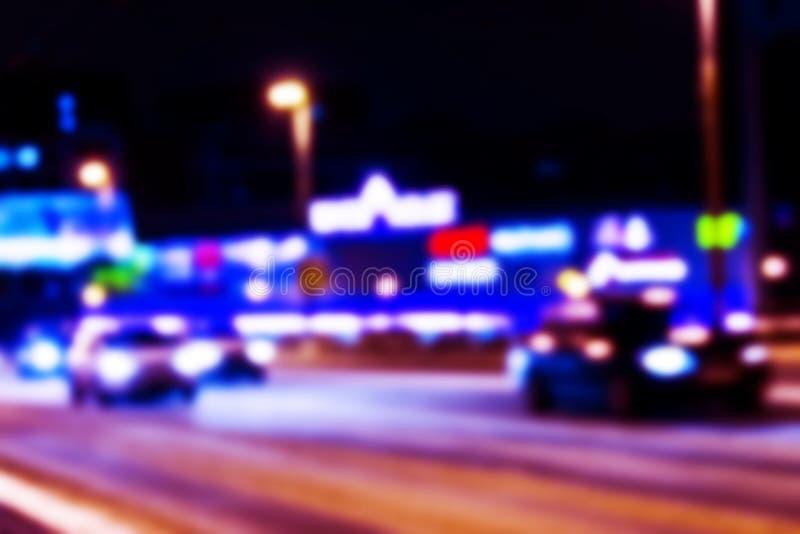 Nattstadssikt i suddighet Oskarpt foto för stadshastighetstrafik Bild för bokeh för gataliv Gatasikt med trafik och defocused bil royaltyfri foto