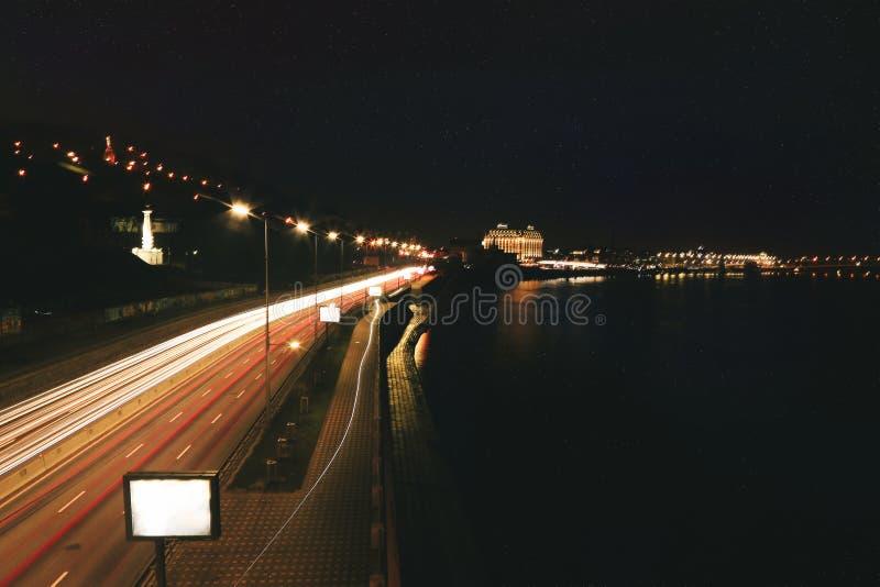 Nattstadsvy med flod, väg, byggnader och ljus Kiev, Ukraina royaltyfri foto