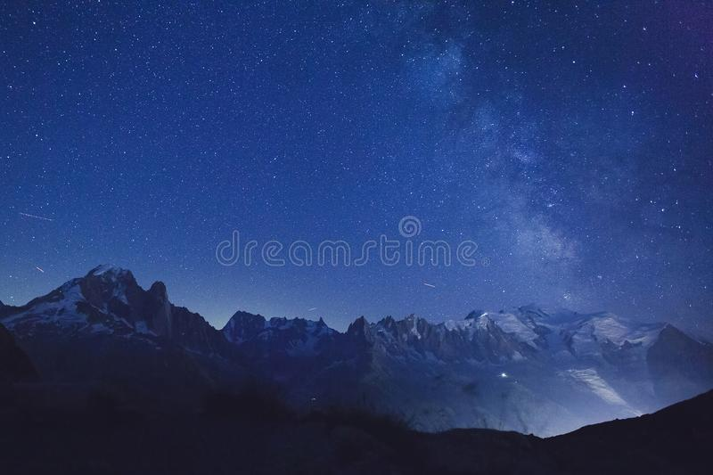 Nattstjärnor och mjölkaktig väg över alpina berg arkivfoto