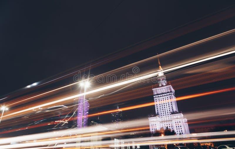 Natttrafikväg i stad med ljusa slingor av bilar - Warszawa - moderna skyskrapor fotografering för bildbyråer