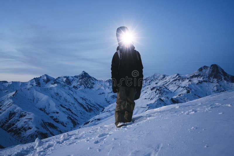 Nattutforskare, med en pannlampa som framme står av fantastisk vinterbergsikt Modig handelsresande med ryggsäcken och snowboarden arkivfoto