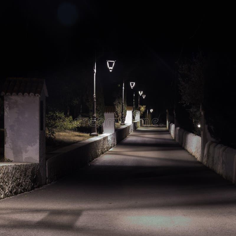 Nattväg som är upplyst vid lyktstolpar royaltyfria foton