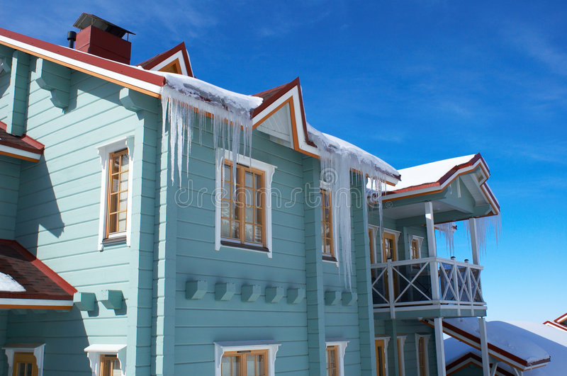 Natty house with icicles. Natty blue house with icicles stock photo