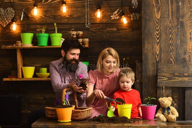 natur för kvinna-, man- och pysbarnförälskelse Bevattna för blommaomsorg Jordgödningsmedel Familjdag växthus Lyckligt fotografering för bildbyråer