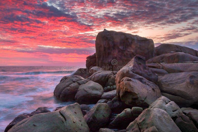 Natur-Meerblick mit rauen Flusssteinen und Wellen bei buntem Sonnenaufgang mit brennendem Himmel stockfotos