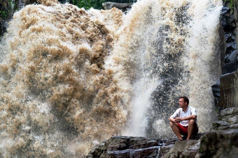 Natur, turism och folkbegrepp Den unga caucasian turisten som bär rött kort och vitt t-skjorta sammanträde på stort, vaggar arkivbilder