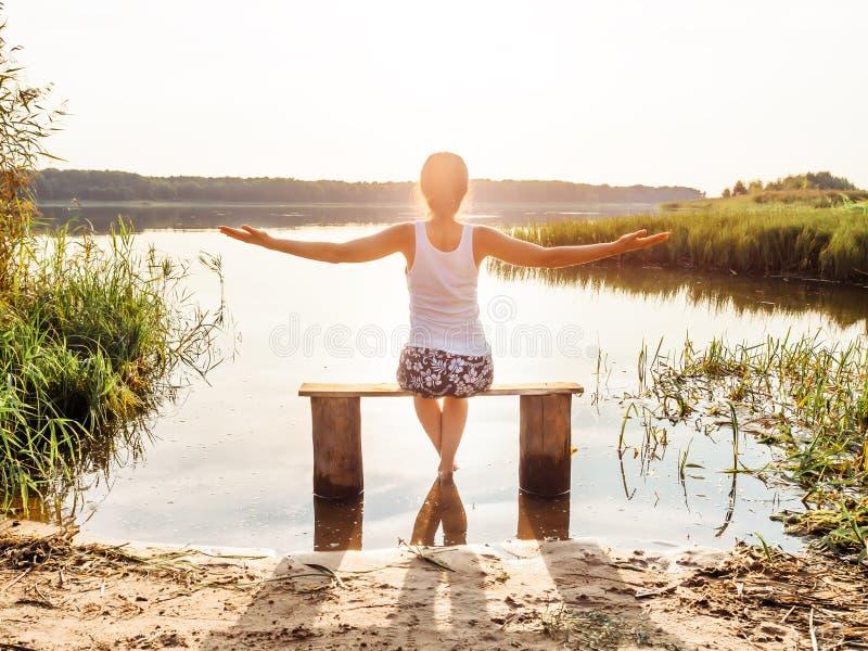 Natura aperta di libertà delle mani della ragazza La ragazza si siede su un banco dal fiume e gode di bello tramonto Ragazza che  fotografia stock libera da diritti