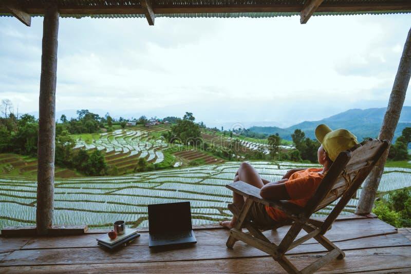 Natura asiatica di viaggio della donna Rilassi leggono un libro nell'amaca il balcone della località di soggiorno Vista del campo immagini stock libere da diritti