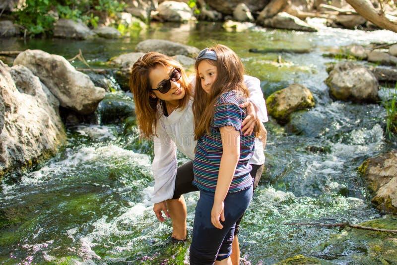 Natura d'esplorazione della figlia e della donna insieme ad una corrente o ad un fiume fotografia stock