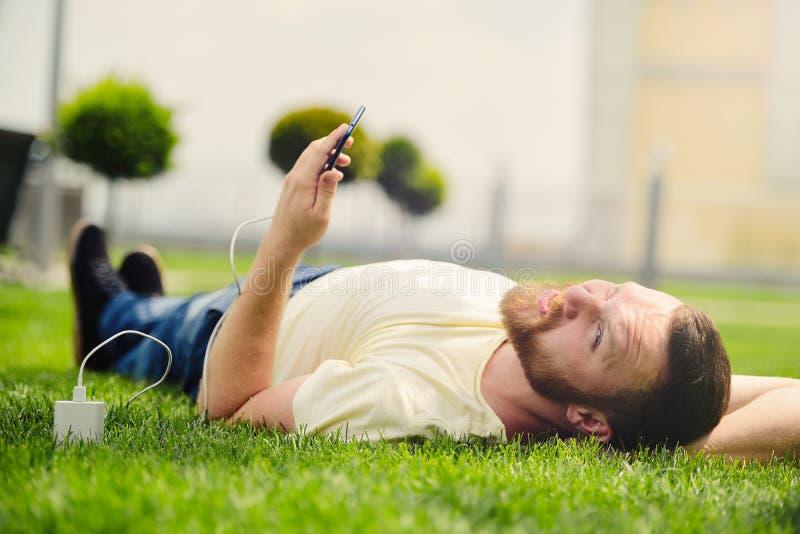 Natura e tecnologia Un uomo con una barba si trova su un'erba verde con uno smartphone in sue mani è sguardi della banca di poter immagine stock libera da diritti